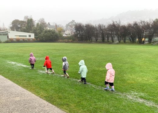 Early Leaning Children playing in Puddles in Raincoats
