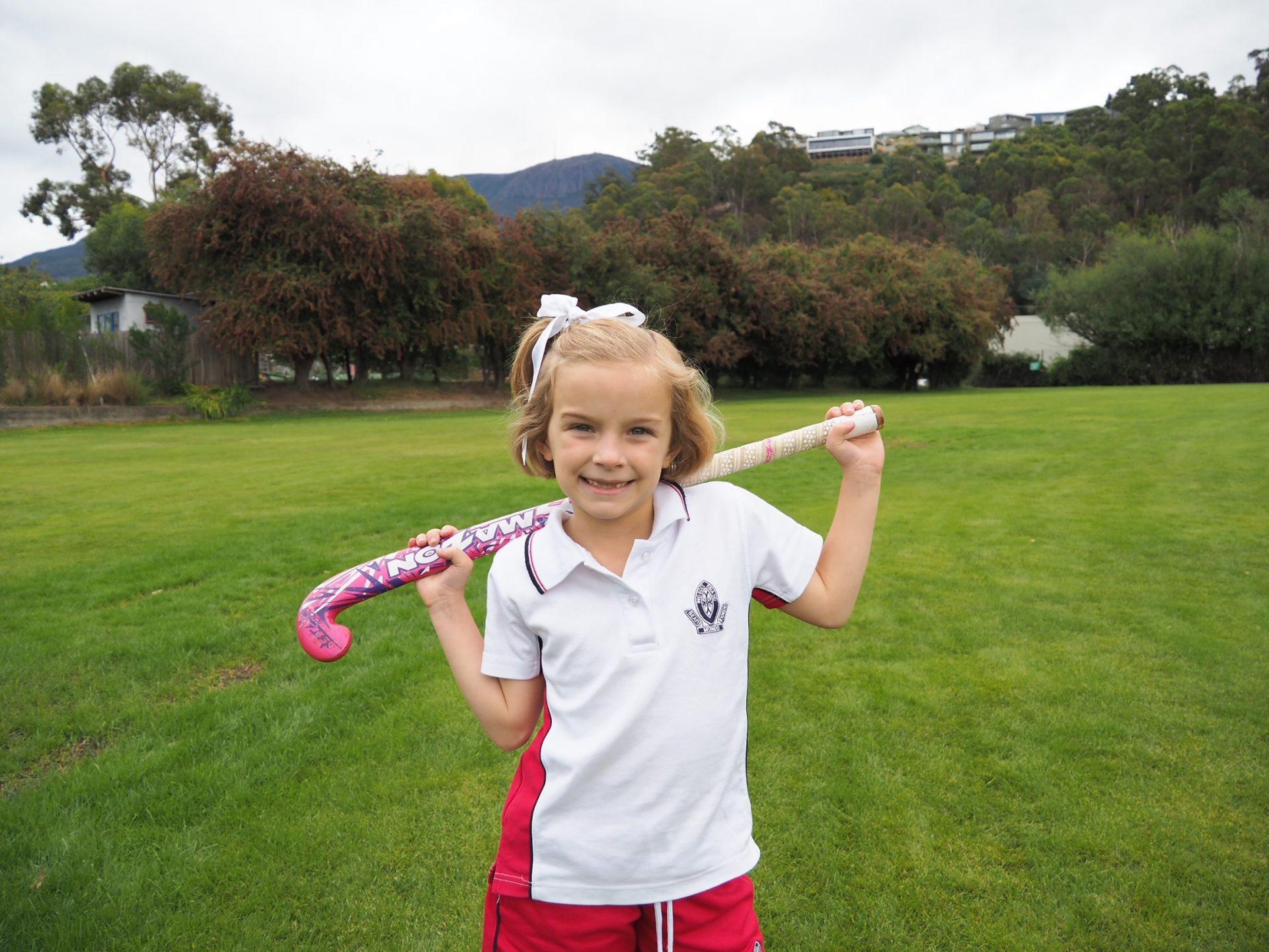 Student posing with Hockey Stick